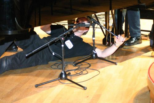 Adjusting the microphone under the grand piano